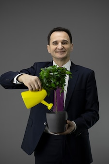 Happy businessman waters green plant from watering can startup, business growth