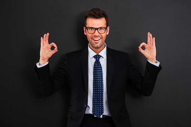 Felice imprenditore con gli occhiali che mostra segno ok