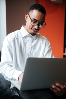 Happy businessman wearing glasses sitting near window and typing by laptop computer