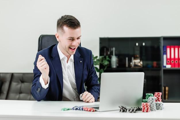 幸せなビジネスマンが職場のオフィスでポーカーをプレイしながらオンラインカジノで勝ちます