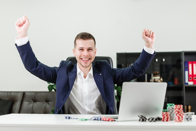 Happy businessman wins in online casino while playing poker in the office at workplace