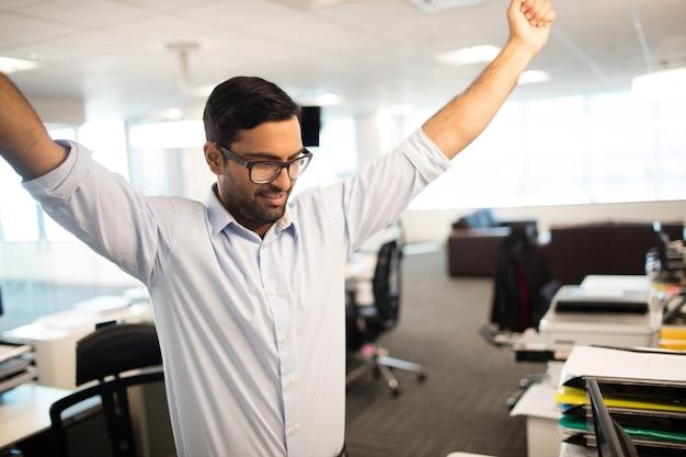 Счастливый бизнесмен с поднятыми руками в офисе