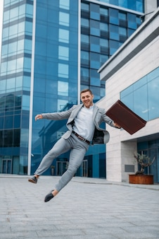 Happy businessman with bicycle at the office building in downtown, urban style