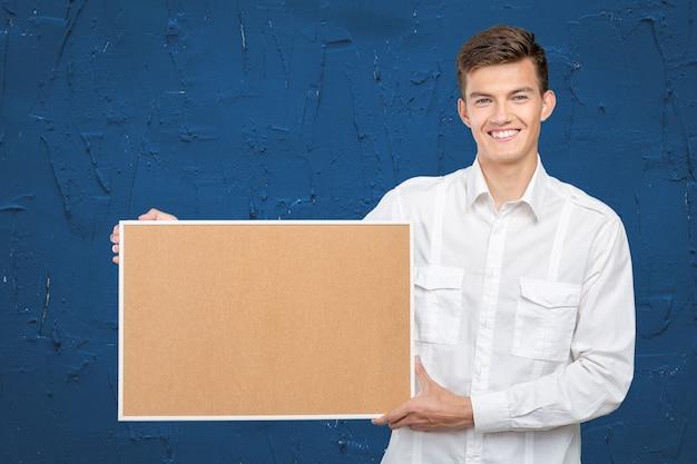 Happy businessman with corkboard