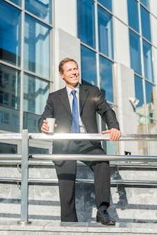 Happy businessman with cup of coffee standing in front of building