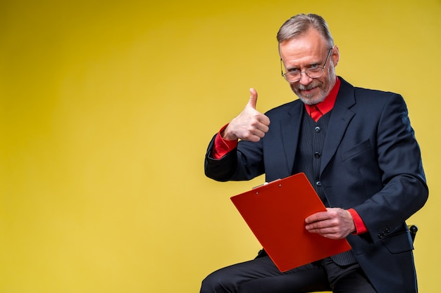 Happy businessman with folder in hand isolated over yellow background. studio shooting. showing ok sign.