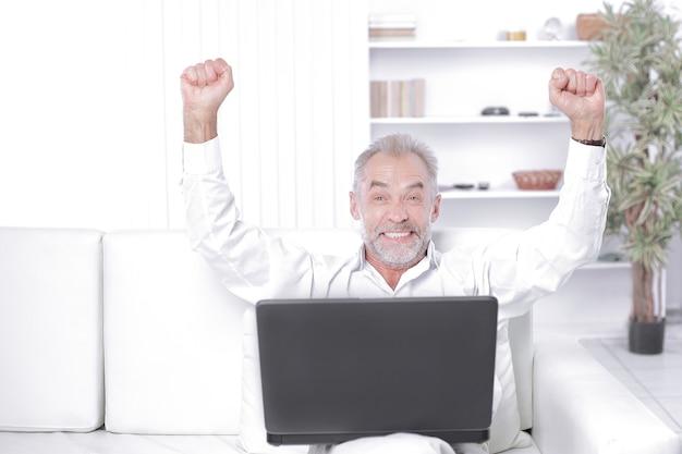 Счастливый бизнесмен с ноутбуком, сидя на софе в офисе.