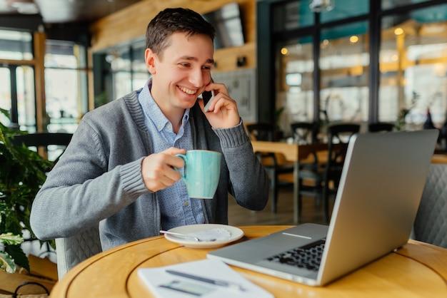 Uomo d'affari felice che lavora al caffè con il computer portatile.