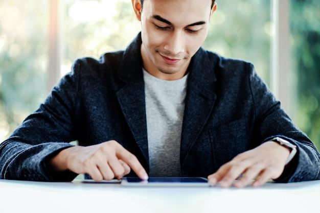 Happy businessman working on digital tablet in office.