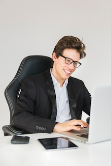 Happy businessman working on laptop at office