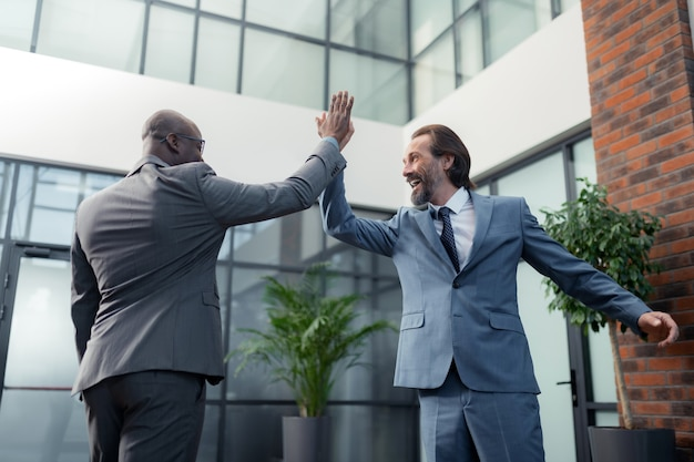 幸せなビジネスマン。彼のビジネスパートナーにハイタッチをしながら笑っている灰色の髪のひげを生やした男
