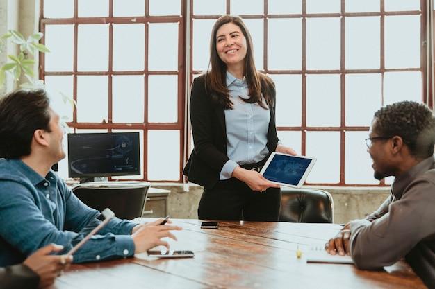 タブレットのモックアップを使用して会議で幸せなビジネスマン