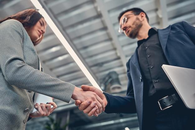 함께 손을 잡고 서있는 동안 로프트 사무실에서 일하는 양복 드레스를 입고 행복한 사업가