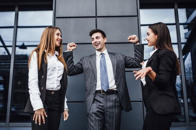 Persone d'affari felici con le mani alzate che vincono la concorrenza finanziaria! concetto di affari! buona fine dei lavori!