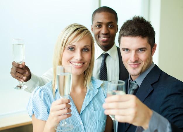 オフィスでシャンパンで幸せな仲間たち