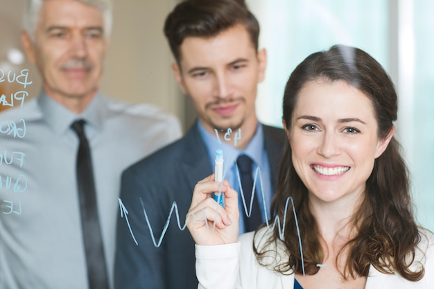 Happy businesswoman drawing graph on glass screen