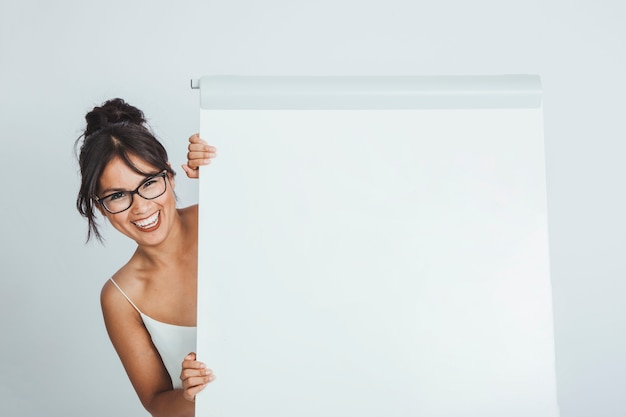 Happy businesswoman hiding behind the whiteboard