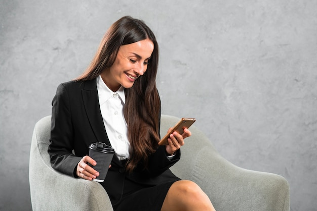 Happy businesswoman holding disposable coffee cup looking at cellphone