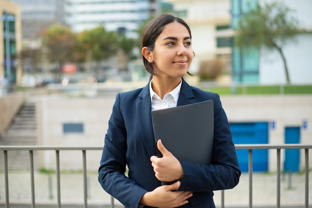 Happy businesswoman holding folder