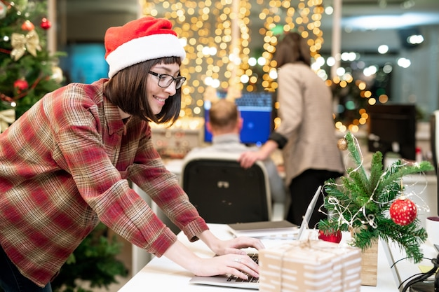 クリスマスの日に来年の仕事を整理しながら、ラップトップの前でタイピングサンタキャップの幸せな実業家