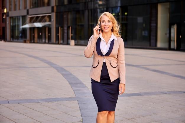 비즈니스 센터 근처 전화로 정장 회담에서 행복 한 사업가