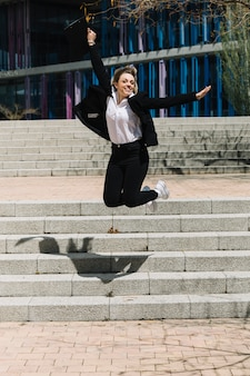 Happy businesswoman jumping in front of stairs