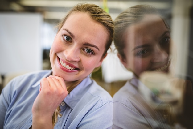 Happy businesswoman leaning on glass