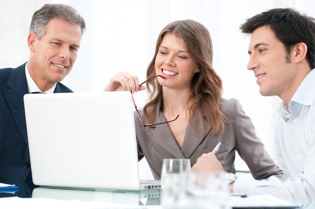 オフィスで彼女の同僚とcoputerを見て幸せな女性実業家