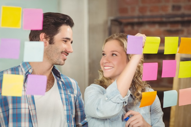 Happy businesswoman looking at colleague in office