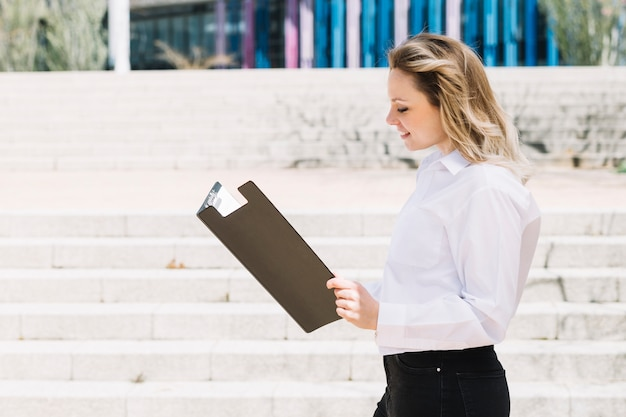 Happy businesswoman looking in folder outdoors