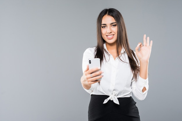 Happy businesswoman making selfie photo on smartphone or making video call on white