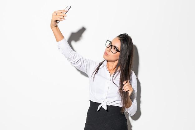 Felice imprenditrice rendendo selfie foto sullo smartphone su bianco