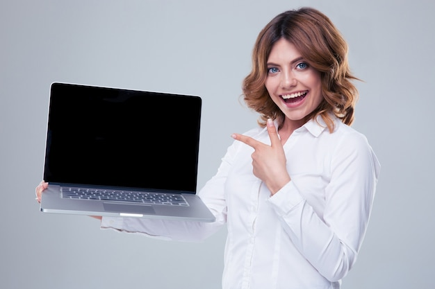 Happy businesswoman pointing finger on laptop screen