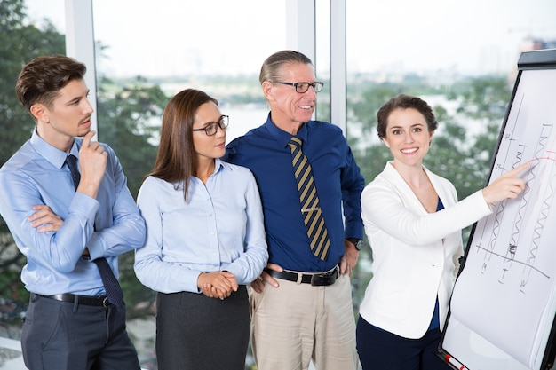 Happy businesswoman presenting chart to colleagues