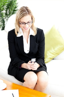 Happy businesswoman sending a text sitting on the sofa