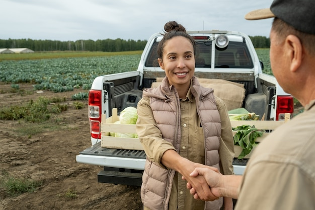 Happy businesswoman shaking hand of mature farmer