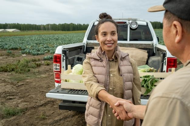 Счастливая деловая женщина, пожимая руку зрелого фермера