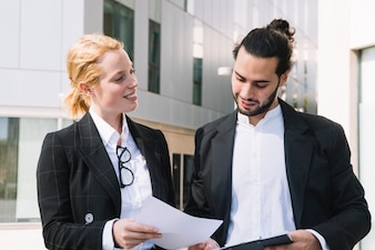 Happy businesswoman showing document to businessman