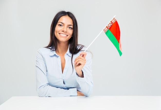 책상에 앉아 흰색 배경에 고립 된 미국 국기를 들고 행복 한 사업가