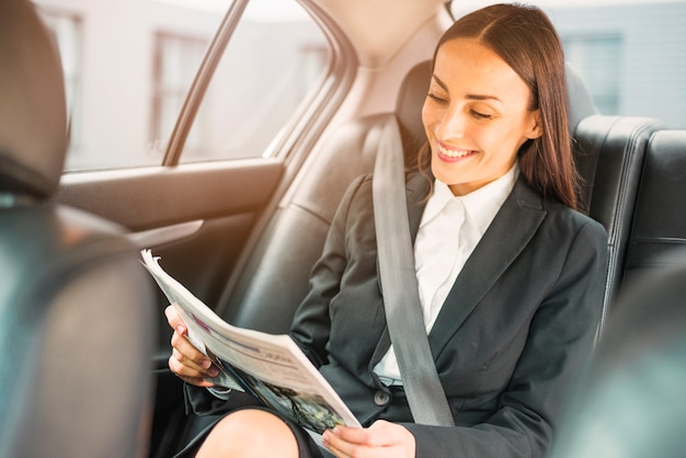 Happy businesswoman sitting inside car reading newspaper