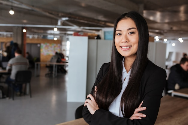 Happy businesswoman standing with arms crossed in office