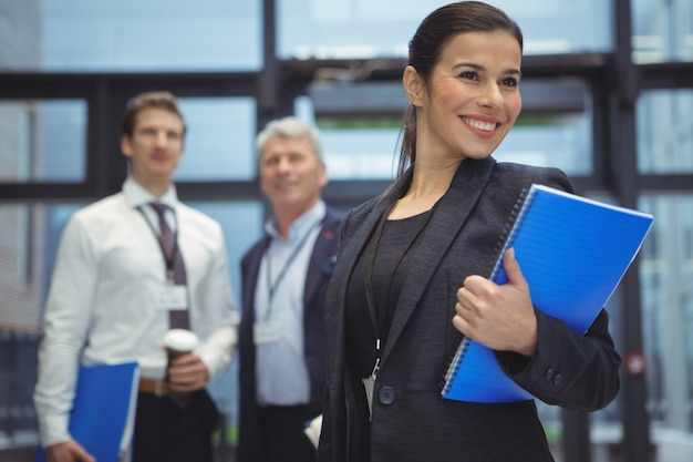 Happy businesswoman standing with notebook