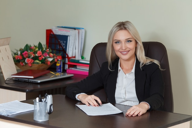 Happy businesswoman in suit smiling and looking at camera