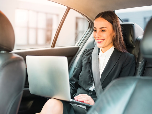 Happy businesswoman traveling by car using laptop