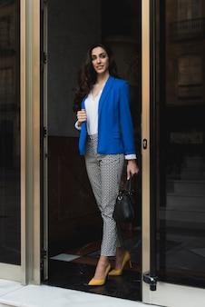Happy businesswoman walking in the vestibule