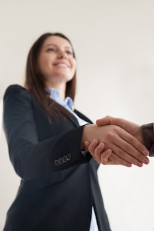 男性の手を振って、握手に焦点を当てるスーツを着て幸せな女性実業家