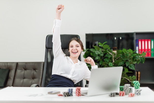 Happy businesswoman wins in online casino while playing poker in the office at workplace