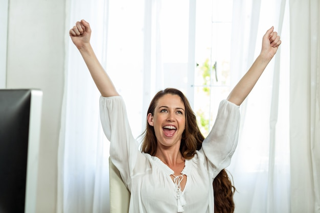 Happy businesswoman with arms raised in office