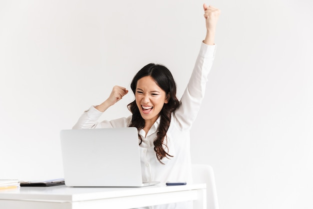 Happy businesswoman with long dark hair screaming with raised arms while working with documents and laptop
