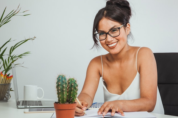 Happy businesswoman with pencil and notebook